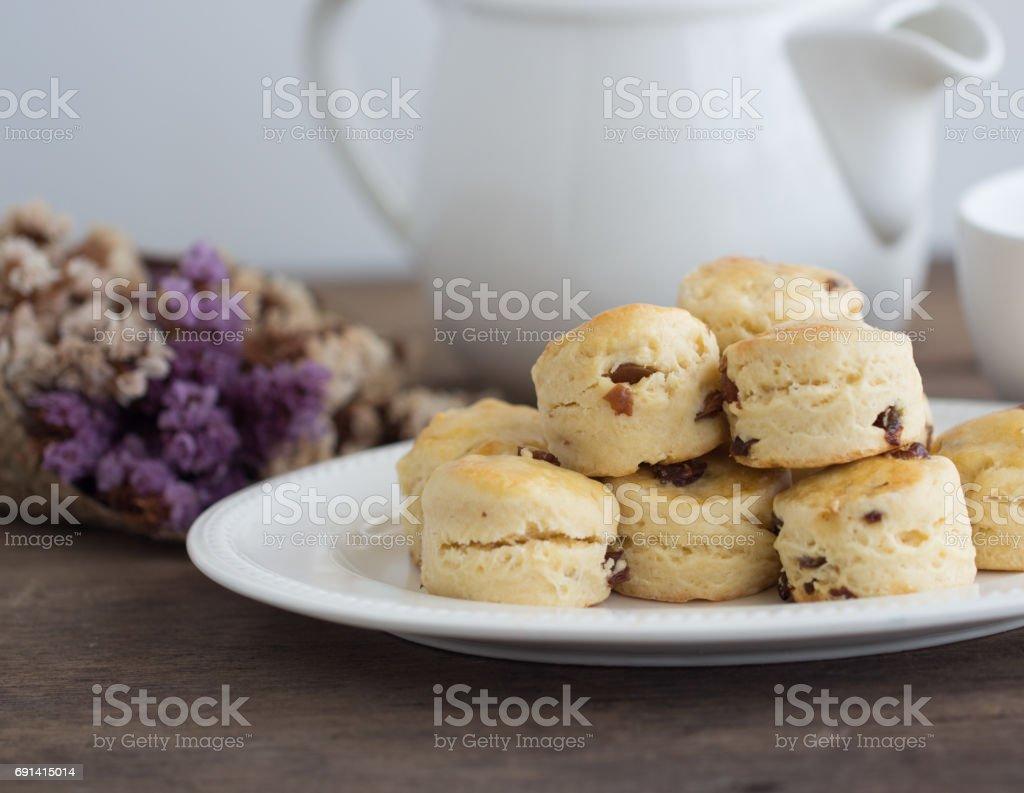 Homemade raisin scones serve with homemade strawberries jam,clotted cream and tea.Scones is English pastry for afternoon tea,cream tea.Delicious scones Devon shire or Cornish cream style. stock photo