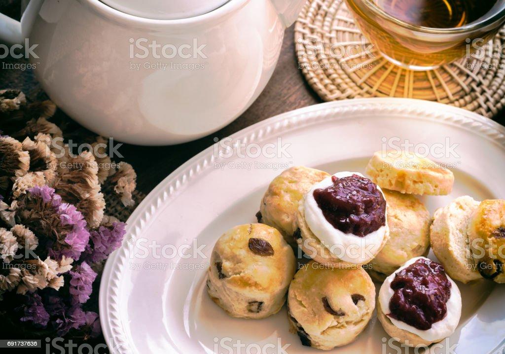 Homemade raisin scones serve with homemade strawberries jam,clotted cream and tea. Set of cream scones on white plate. Scones is English pastry for afternoon tea,cream tea. Devon shire scones and Cornish cream scones. stock photo