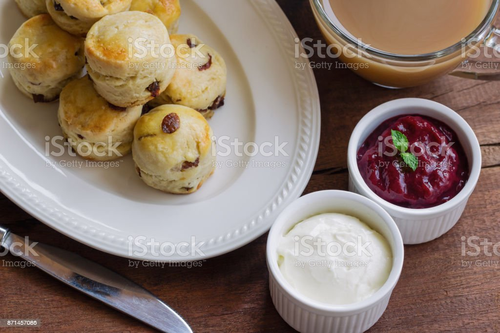 Homemade raisin scones serve with homemade strawberries jam,clotted cream and tea in top view. Scones is English pastry for afternoon tea or coffee break so delicious and classic. Vintage tone style. stock photo