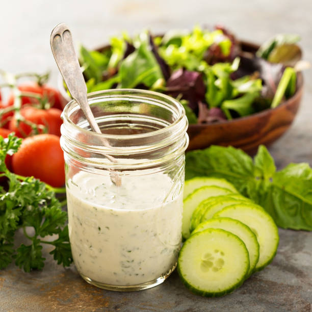 Homemade ranch dressing in a mason jar Homemade ranch dressing in a mason jar with fresh vegetables salad dressing stock pictures, royalty-free photos & images