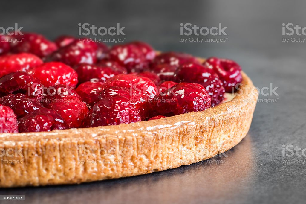 Homemade raspberries pie tart baked shot on grey abstract background stock photo