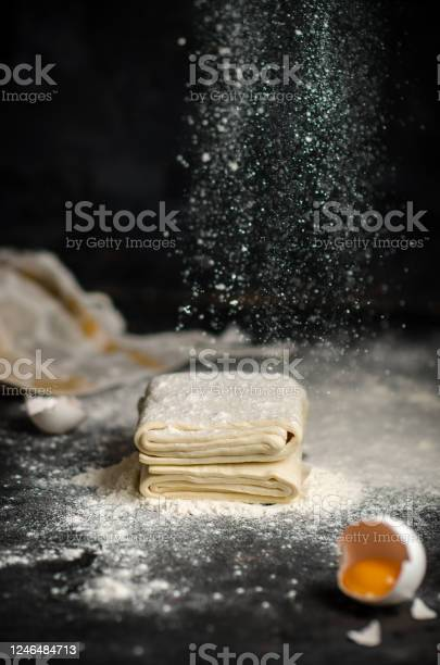 Photo of Homemade raw puff pastry on black background