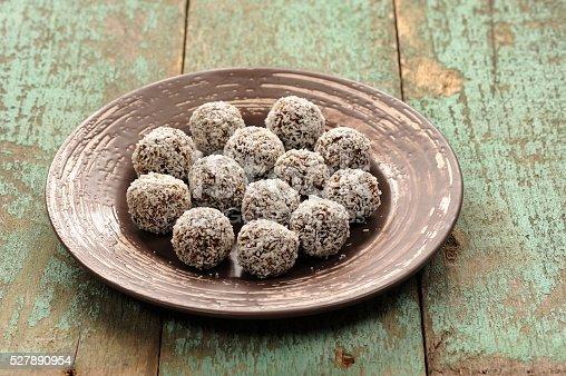 istock Homemade raw vegan sweets in coconut shavings in ceramic plate 527890954