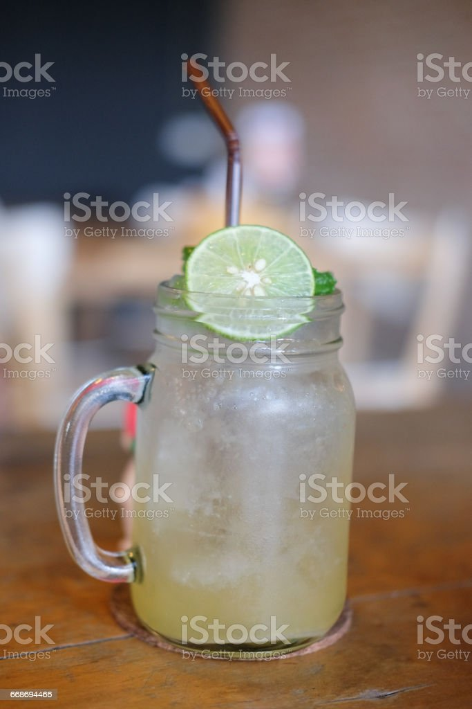 Homemade refreshing drink with lemon slices on wood table stock photo