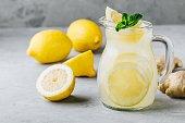 Homemade refreshing summer lemonade drink with lemon slices, ginger, mint and ice