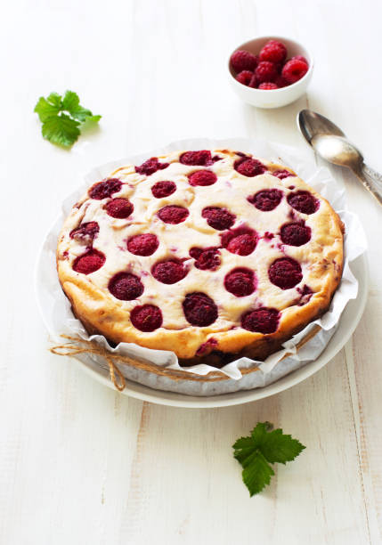 Homemade ricotta casserole with raspberries on white wooden background close up stock photo