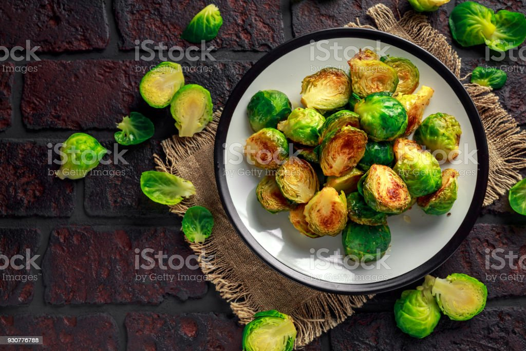 Homemade Roasted Brussel Sprouts with Salt, Pepper on a old stone rustic table stock photo