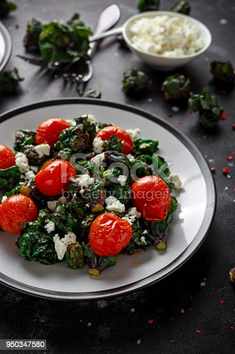 istock Homemade Roasted Green Kalettes salad with cherry tomatoes and feta cheese. healthy food 950347580