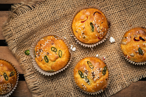 Homemade salty rustic muffins with cheese pepper and vegetables golden baked and served on a plate
