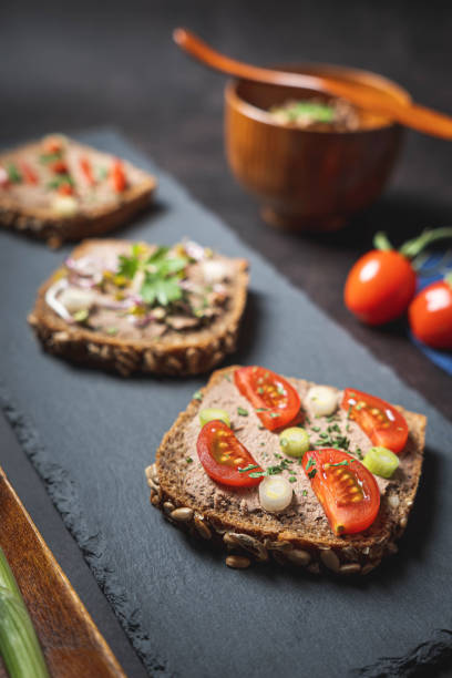 Homemade Rustic Pate on Bitten Slice of Bread with Fresh Vegetables stock photo