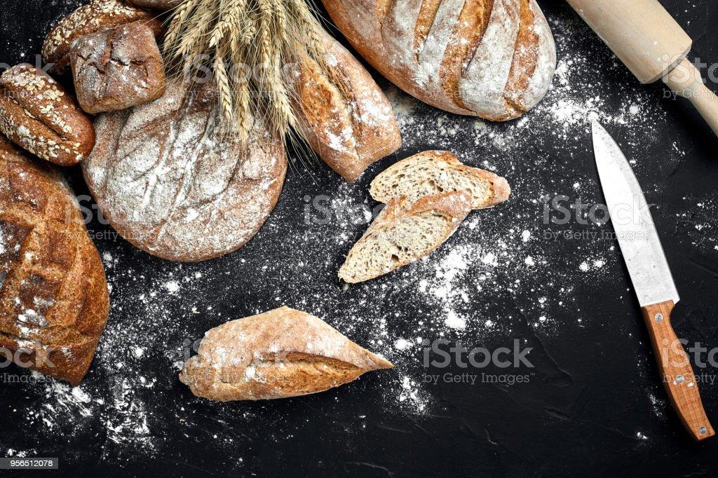 Hausgemachtes Schwarzbrot bestreut mit Mehl und verschiedene Körner und Samen auf einem schwarzen Hintergrund mit Ährchen von Weizen oder Roggen und Hafer - Lizenzfrei Alt Stock-Foto