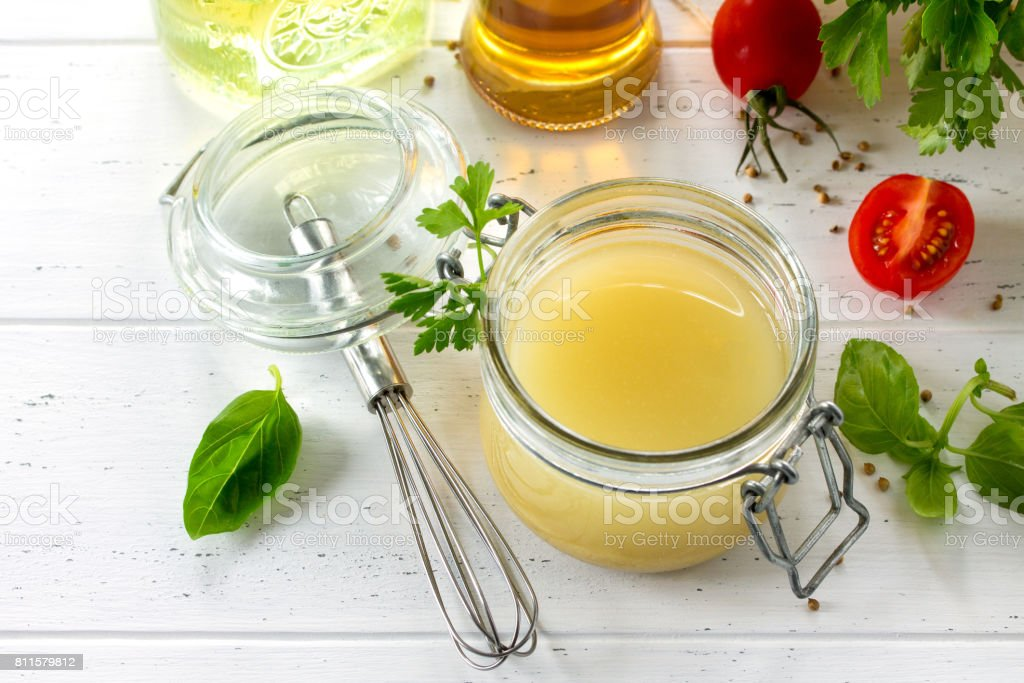 Homemade salad dressing vinaigrette with mustard, olive oil, lemon juice and various fresh vegetables and herbs on a wooden background. The concept of a healthy diet and detox diet. stock photo