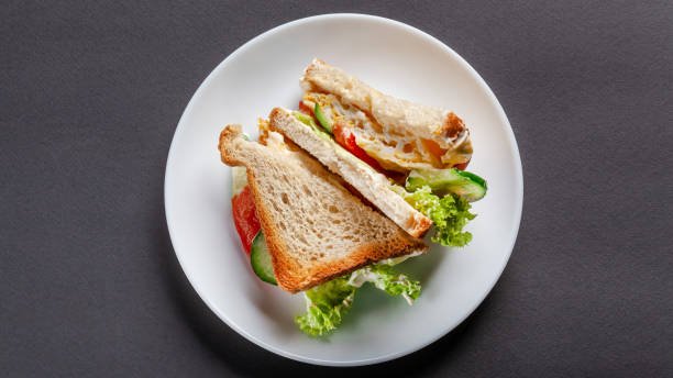 Homemade sandwich made of toast bread, fried egg, melted cheese, tomatoes, cucumber, lettuce, burgers and mayonnaise sauce. Sandwich on a white plate, on a black background. top view