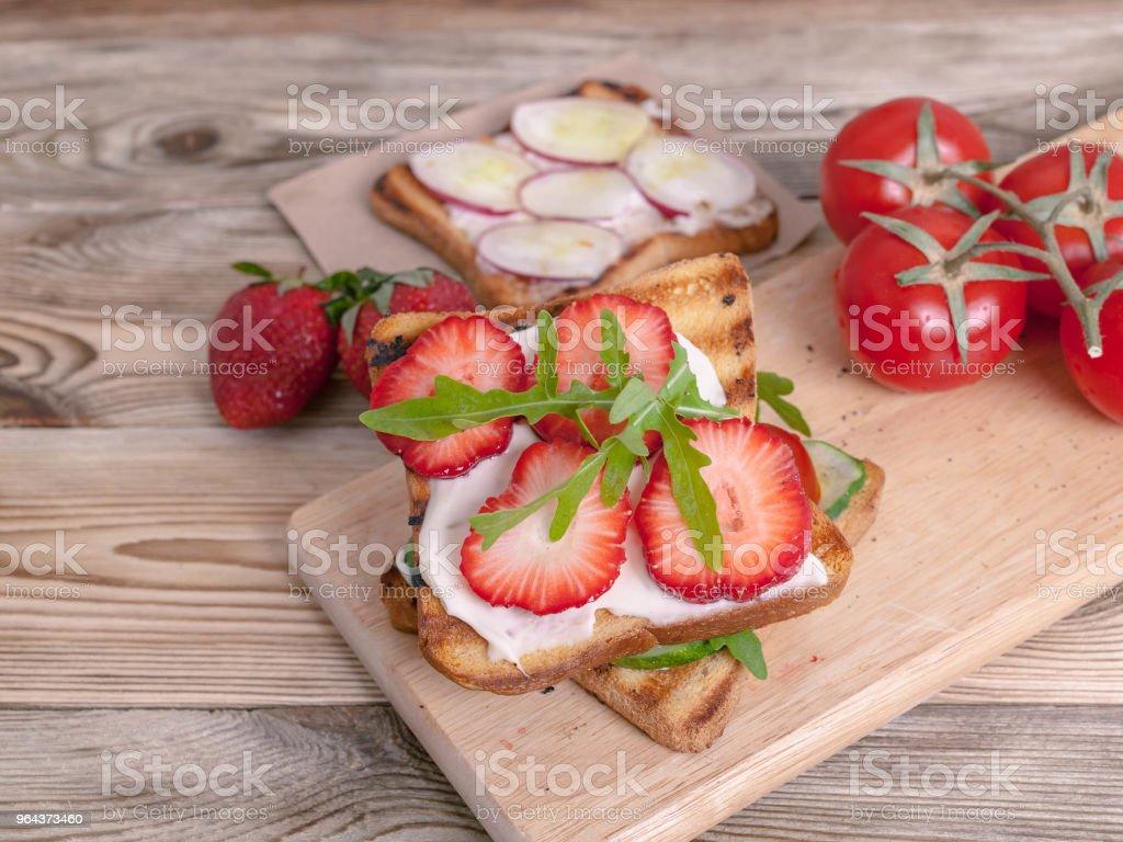 Zelfgemaakte broodjes met verse aardbeien en groenten op een houten achtergrond. Vegetarische maaltijden - Royalty-free Aardbei Stockfoto