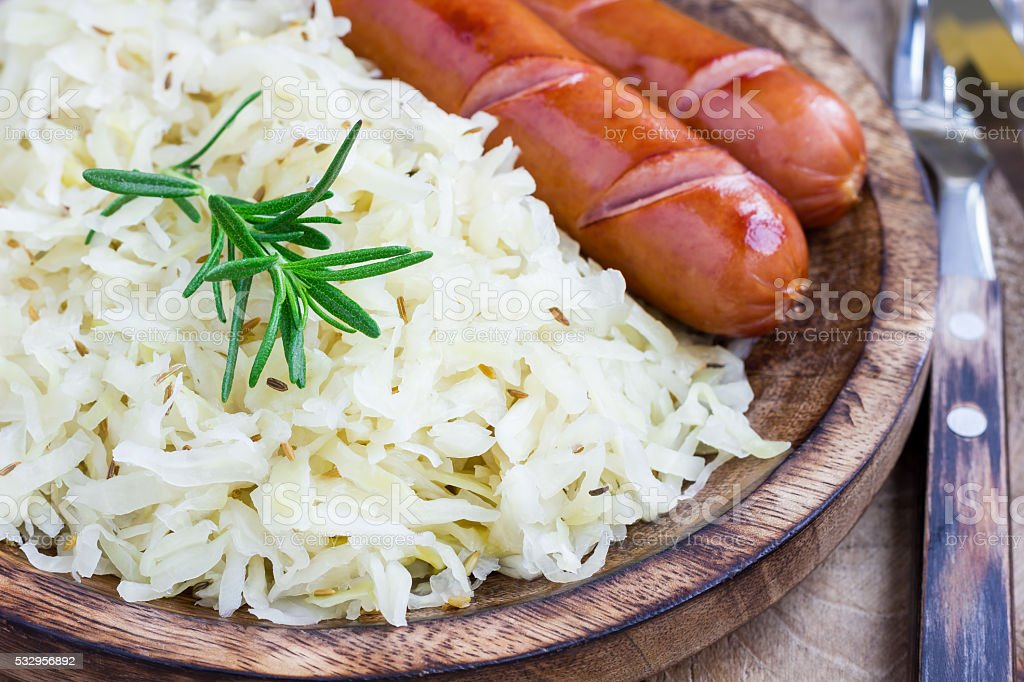 Homemade sauerkraut with sausages on a wooden plate stock photo