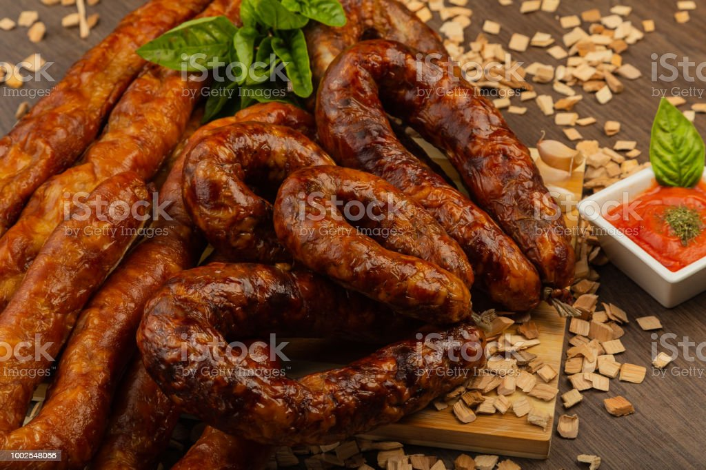 Homemade sausage on a wooden background with seasonings and sauce royalty-free stock photo