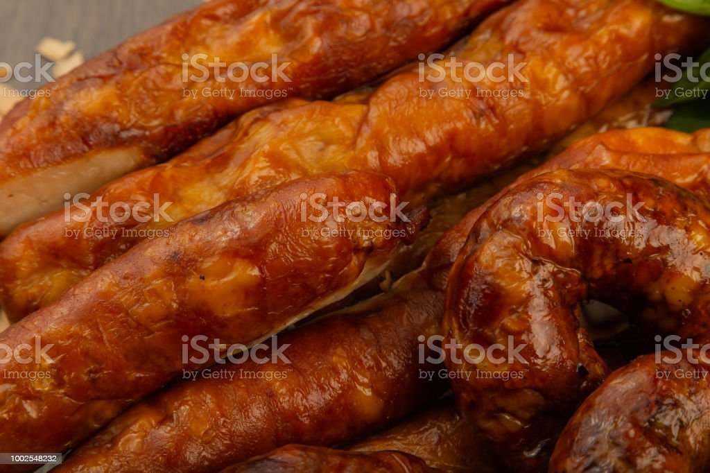 Homemade sausage on a wooden background with seasonings and sauce - Stock image .