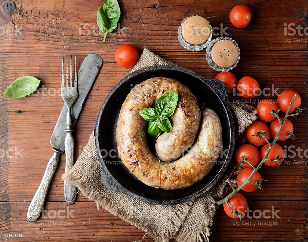 homemade sausages in a pan on a wooden background stock photo