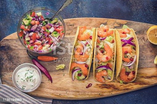 Homemade shrimp tacos with salsa, sour cream, chili pepper and spicy avocado salad