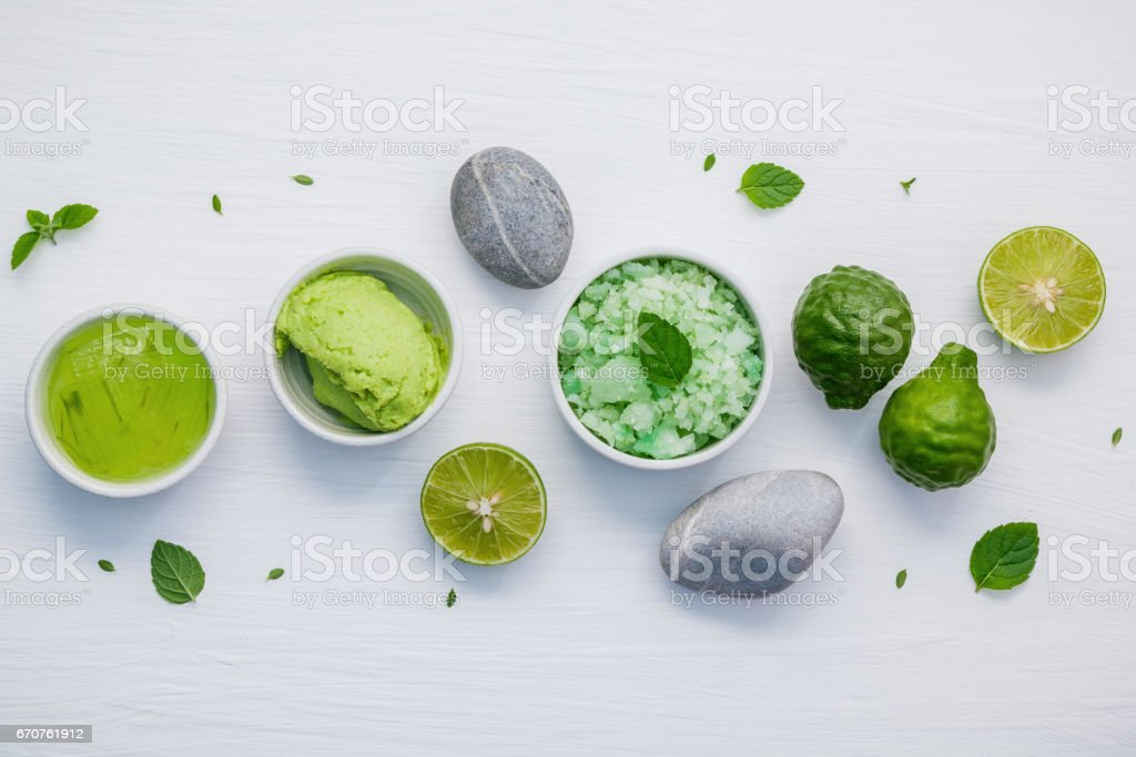 Homemade skin care and body scrubs with green natural ingredients aloe vera ,aromatic salt ,avocado scrub and spa stone set up on white shabby wooden background. Zen spa and oriental spa theme. stock photo