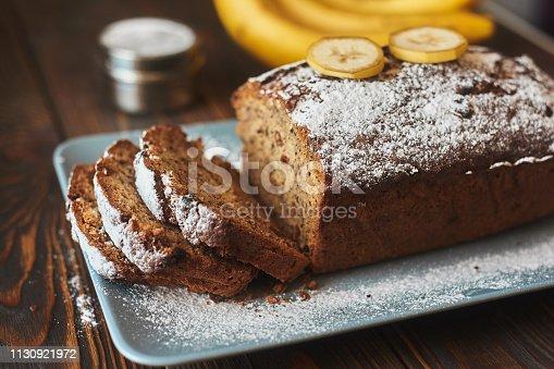homemade sliced banana cake decorated with sugar powder and three banana at wooden background.
