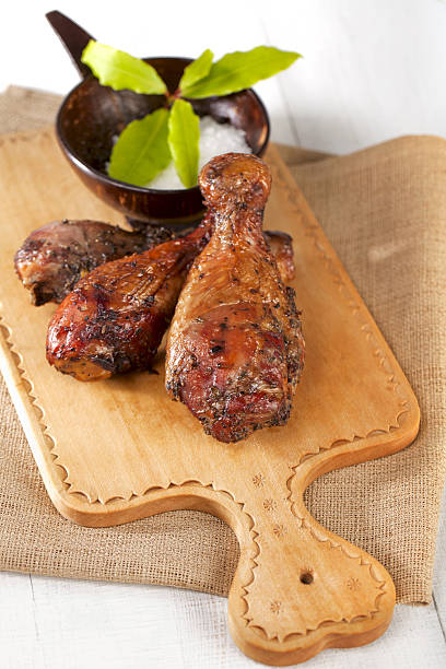 homemade smoked  chicken drumstick on a wood, shallow DOF stock photo