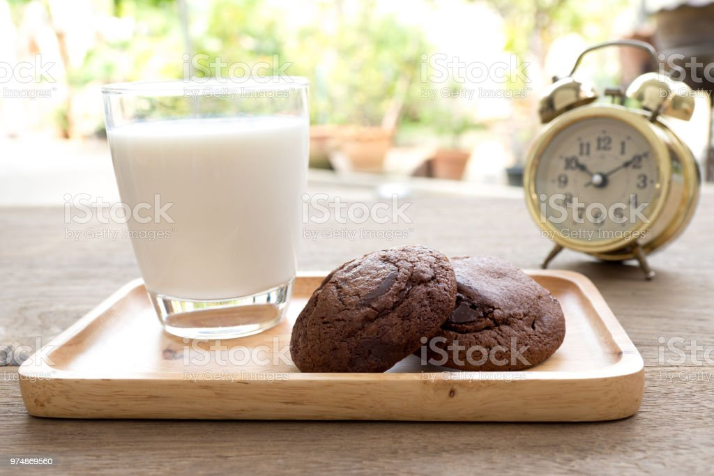 Homemade soft dark chocolate brownie cookies placed on a wooden plate with milk glass on wooden table. Behind cookies have gold vintage alarm clock stock photo