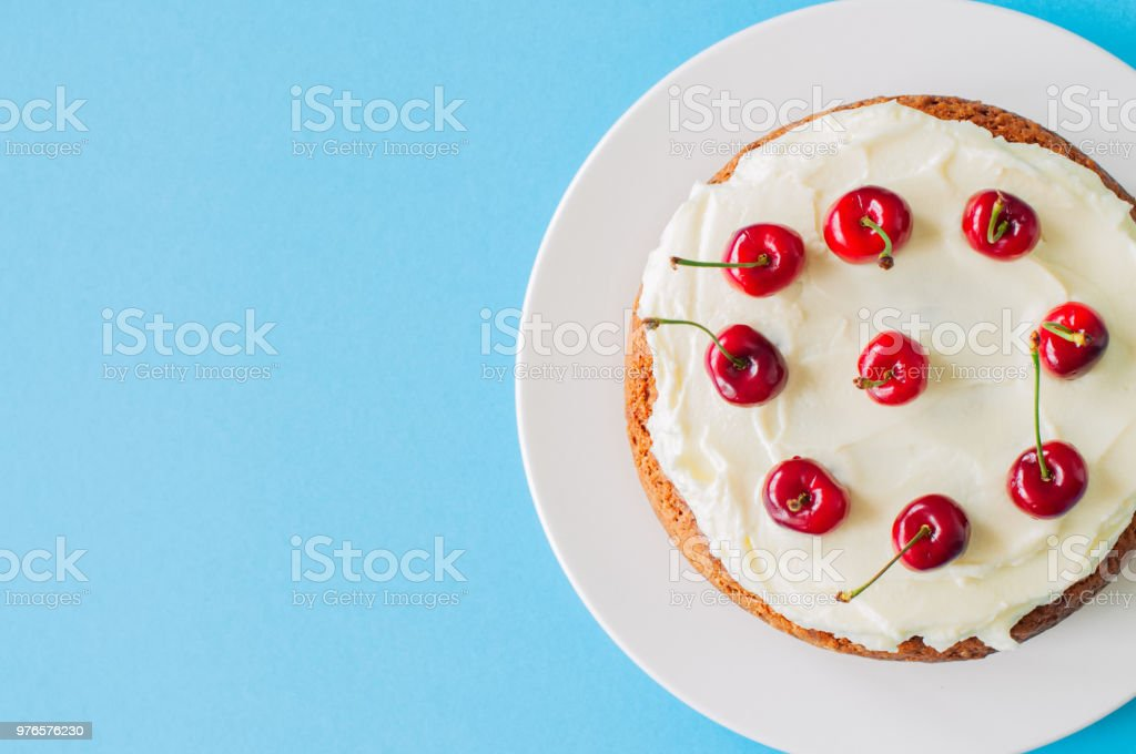 Homemade sour cream cake with cream cheese frosting decorated with fresh ripe cherries on a light blue background. stock photo