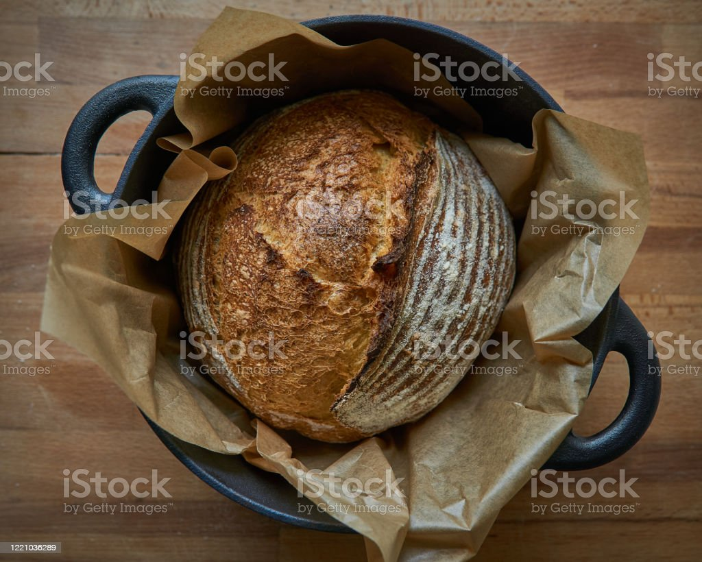 Homemade sourdough bread in a dutch oven on a wooden board. - Royalty-free Bakery Stock Photo