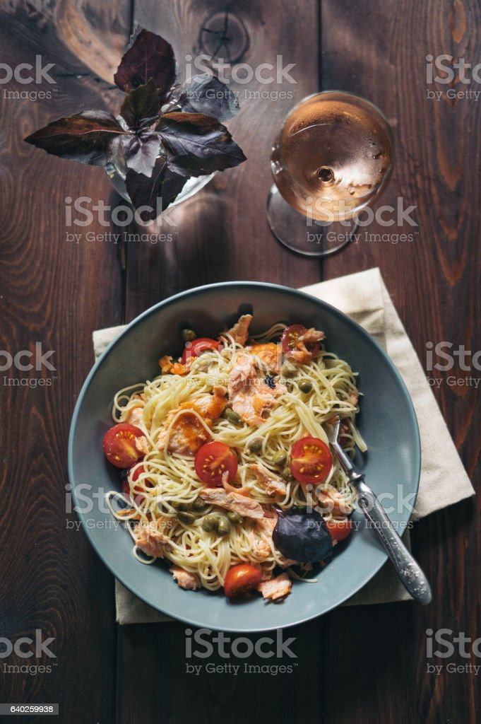 Homemade spaghetti pasta with salmon, tomatoes and capers stock photo