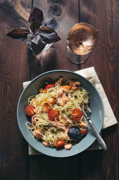 homemade spaghetti pasta with salmon, tomatoes and capers - weinsoße stock-fotos und bilder