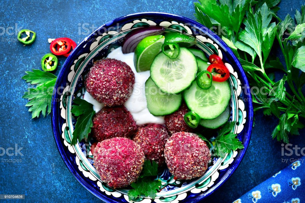 Homemade spicy chickpea beetroot falafel garnished with fresh vegetable and yogurt stock photo