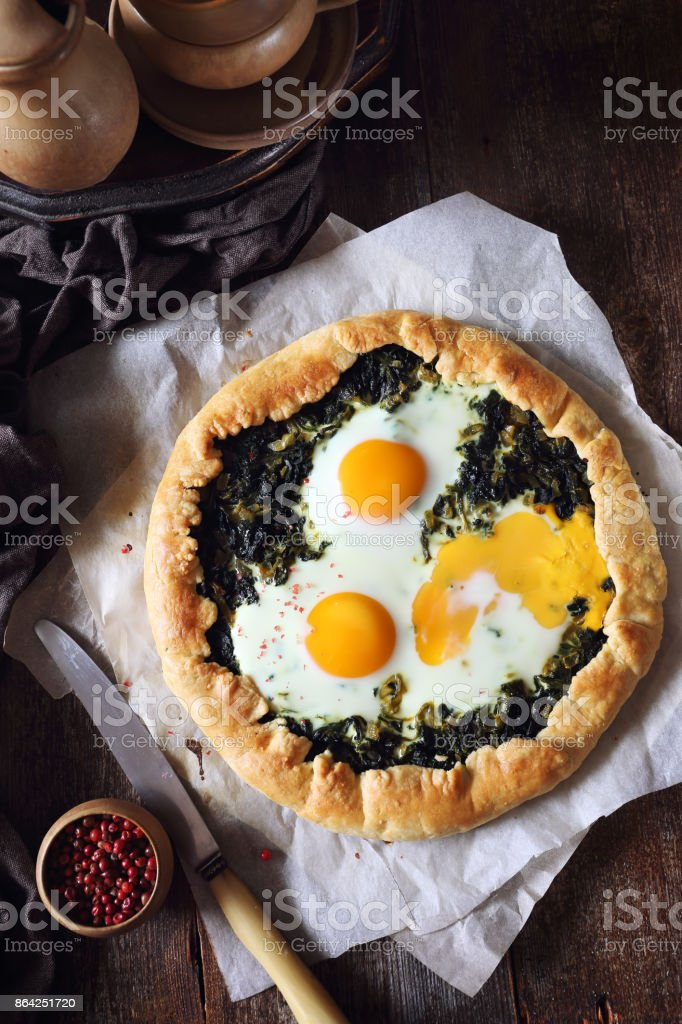 Homemade spinach pie galette with eggs royalty-free stock photo