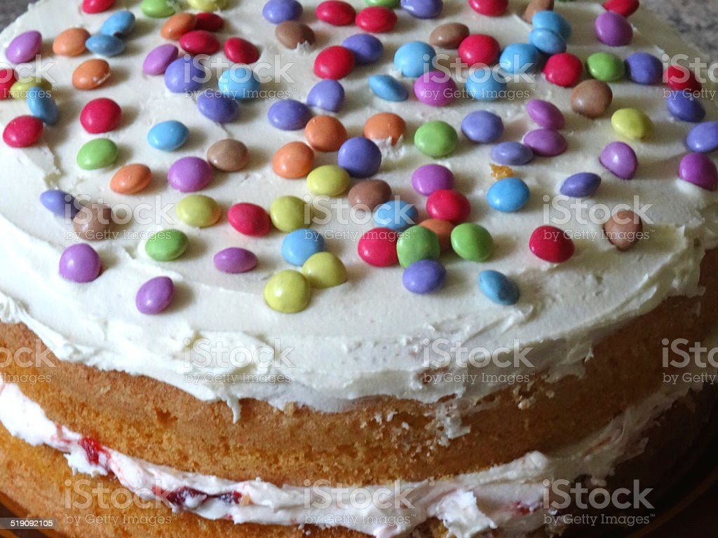 Homemade sponge cake with cream / jam, decorated with icing, chocolate-sweets stock photo