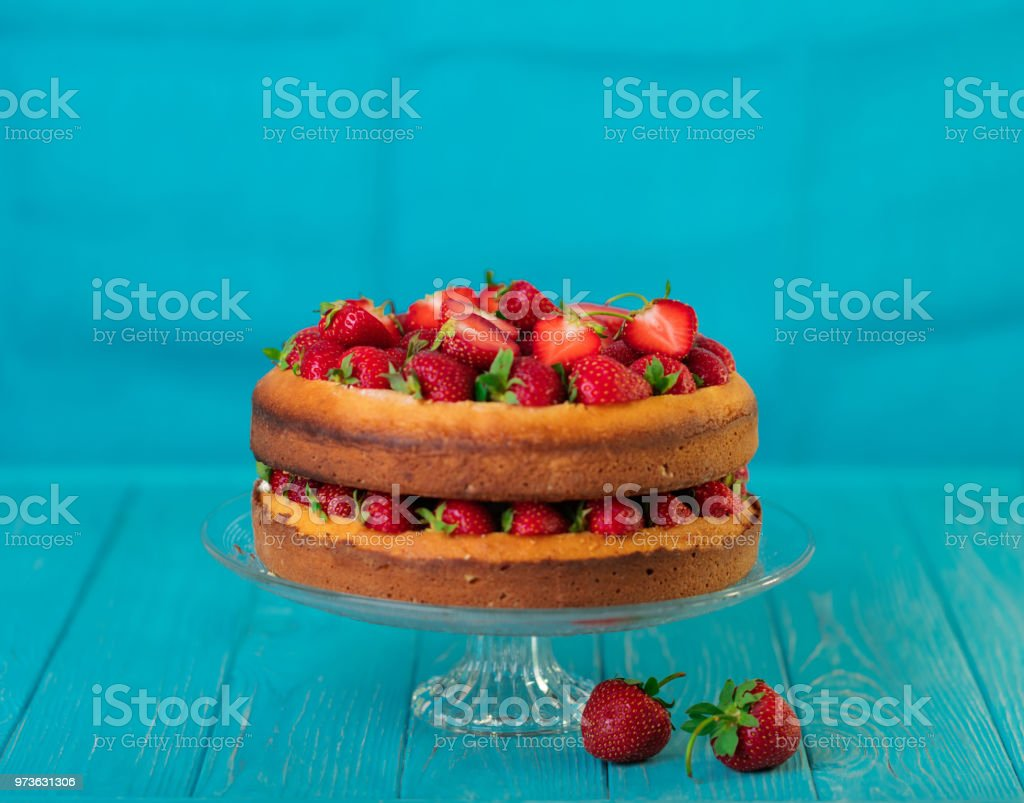 Homemade strawberry cake on a glass stand on the blue background....