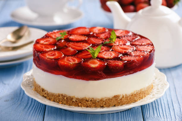 Homemade strawberry cheesecake on blue wooden background. stock photo