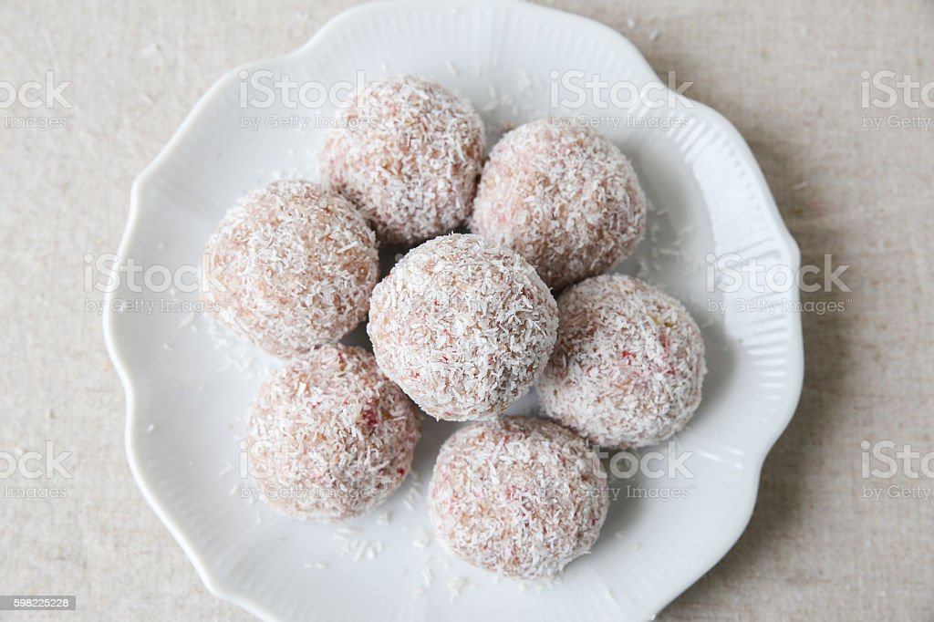 Homemade strawberry, date, cashew and coconut bliss ball on vint foto royalty-free