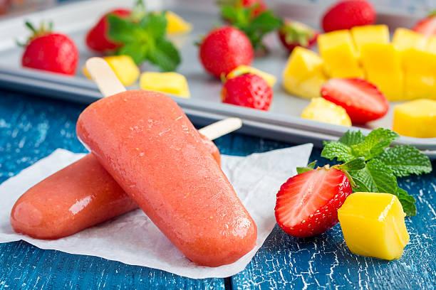 homemade strawberry-mango popsicles on a wooden background - mango eis am stiel stock-fotos und bilder