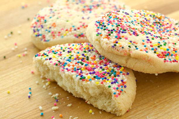 Homemade sugar cookies with color sprinkles Studio photo of homemade sugar cookies with color sprinkles. Selective focus on top of broken cookie in center. sugar cookie stock pictures, royalty-free photos & images