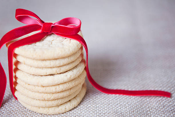 Homemade Sugar Cookies with Ribbon homemade christmas sugar cookies tied with red ribbon. copyspace sugar cookie stock pictures, royalty-free photos & images