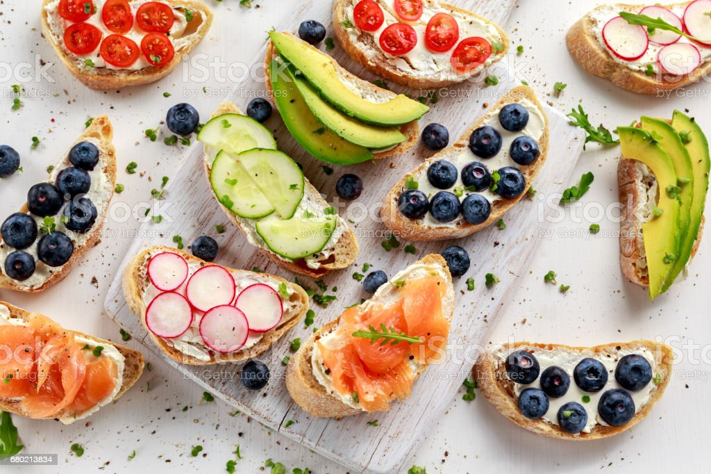Homemade summer toast with cream cheese Smoked Salmon, Blueberries, Radish, Cucumber, Avocado and cress salad. Fresh healthy concept food. stock photo