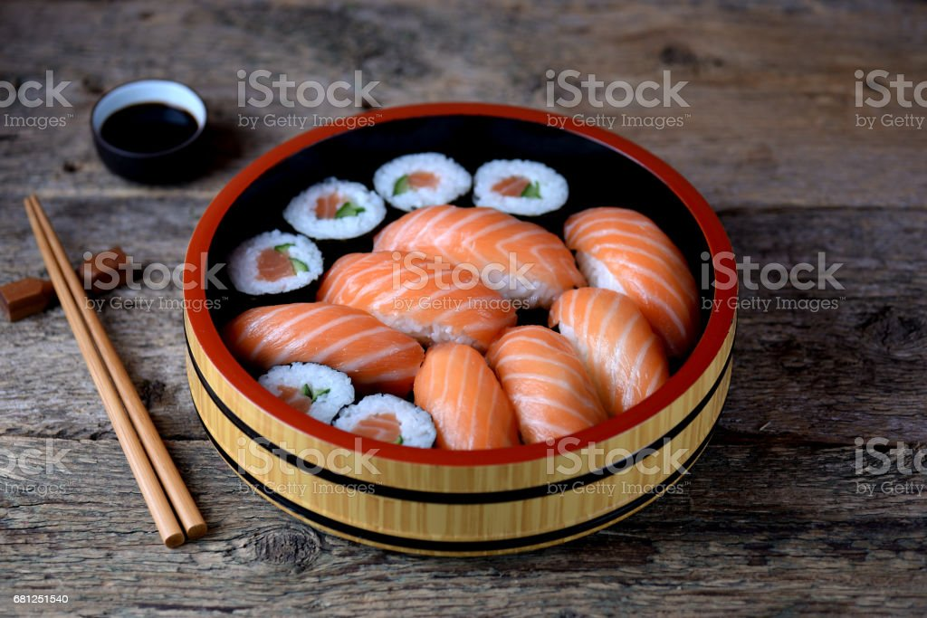 Homemade sushi with fresh salmon and cucumber on old wooden background. royalty-free stock photo