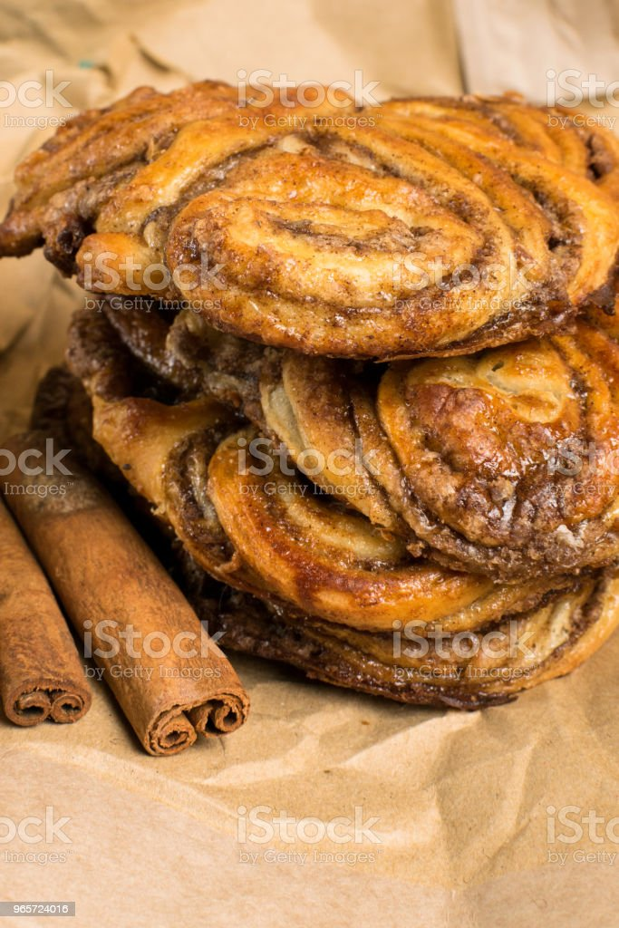 homemade sweet cinnamon rolls on paper bag with sticks of cinnamons - Royalty-free Bag Stock Photo