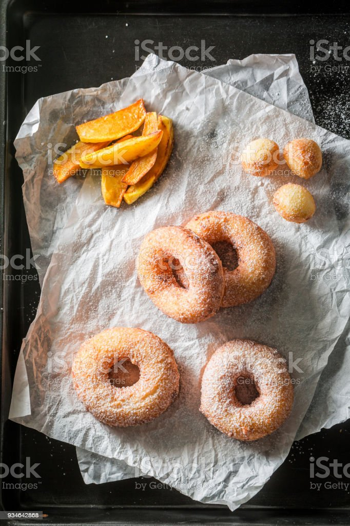Homemade sweet donuts with powdered sugar on paper stock photo