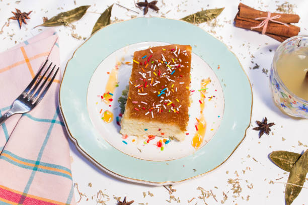 homemade sweet food baba and cup of ginger tea on white table decorated with cinnamon stick and star anise - mimosa cake foto e immagini stock