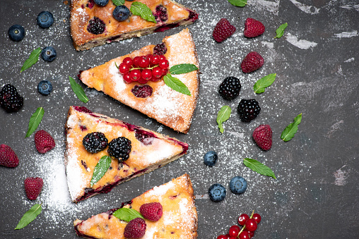 Homemade sweet pie with mixed red berry fruit. Tart dessert slices with currant, raspberry, blackberry and blueberry flat lay tabletop view