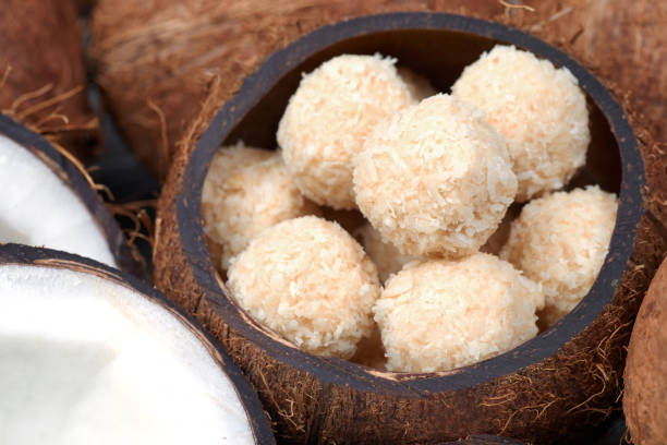 Homemade sweets in a coconut bowl. Toffee and coconut balls stock photo