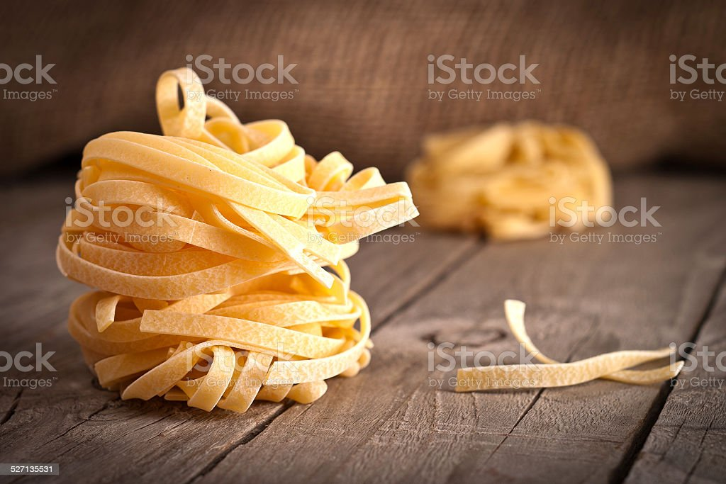 Homemade tagliatelle. Uncooked pasta on the wooden table stock photo