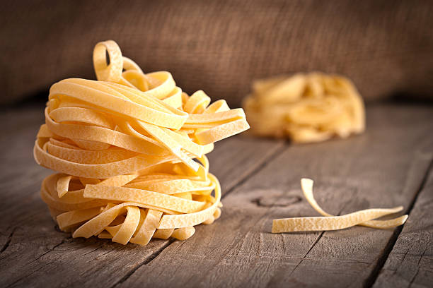 Homemade tagliatelle. Uncooked pasta on the wooden table Homemade tagliatelle. Uncooked pasta on the wooden table. tagliatelle stock pictures, royalty-free photos & images