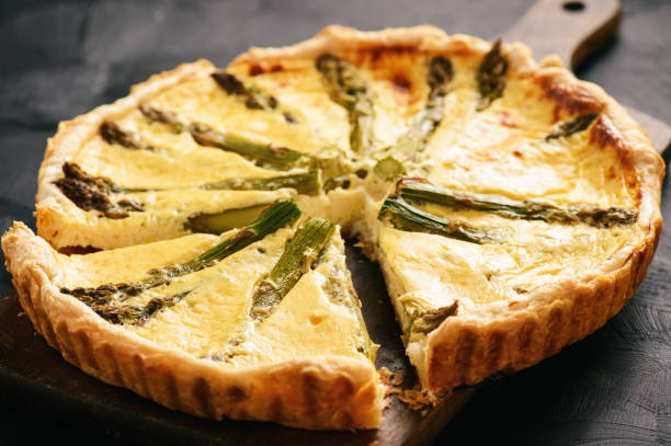 Homemade tart with asparagus and cheese on black background. stock photo